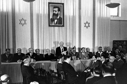 David Ben-Gurion reading the Declaration of the Establishment of the State of Israel on May 14, 1948 in the Dizengoff house in Tel Aviv. To Ben-Gurion's right is Rabbi Yehuda Leib (Fishman) Maimon. Photo: The State of Israel National Photo Collection/Kluger Zoltan