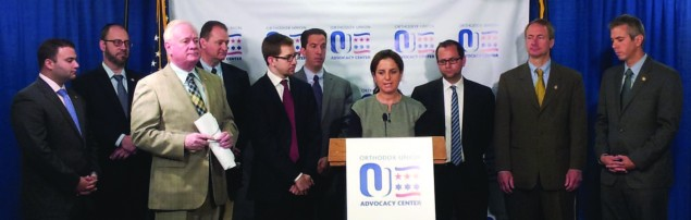 Tamar Eisenstat (center), an OU Advocacy-NY lay leader, discusses the benefits of the Energy Parity Act for Jewish day schools at a press conference in Albany. She is surrounded by members of the New York State Legislature as well as by Jeff Leb (to her left, front row), director of political affairs for OU Advocacy-NY, and Maury Litwack (to her right), director of state political affairs and outreach for OU Advocacy. New York State Senator Simcha Felder is in the back row, second from left.