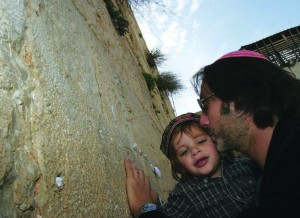 A French immigrant kisses his son as he prays at the Western Wall in Jerusalem after arriving in Israel.