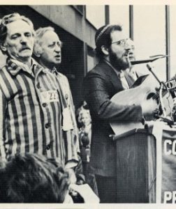 Cantor Goffin performing with his guitar at a Soviet Jewry rally with two Russians dressed in prisoner uniforms, circa 1970. Courtesy of Cantor Goffin