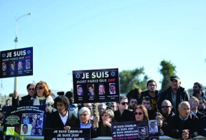 At the funeral of the four victims of the Paris kosher supermarket attack, mourners hold signs showing their solidarity with the victims of the Charlie Hebdo massacre in Paris. Photo: Israel Sun