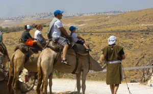 A staff member portraying Eliezer (far right) assists visitors in mounting their camels as they prepare to travel to Avraham's tent.