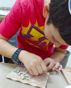 A young boy at The Workshop glues letters onto the base of his candle holder. Photos courtesy of Mandy Broder