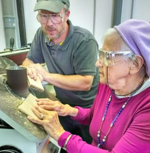 A ninety-year-old woman smooths a piece of wood on the oscillating spindle sander.